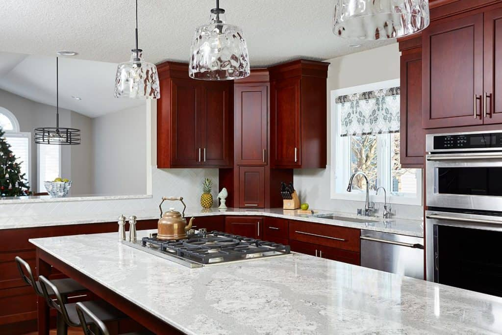 Kitchen island featuring Cambria countertops & a downdraft range hood.