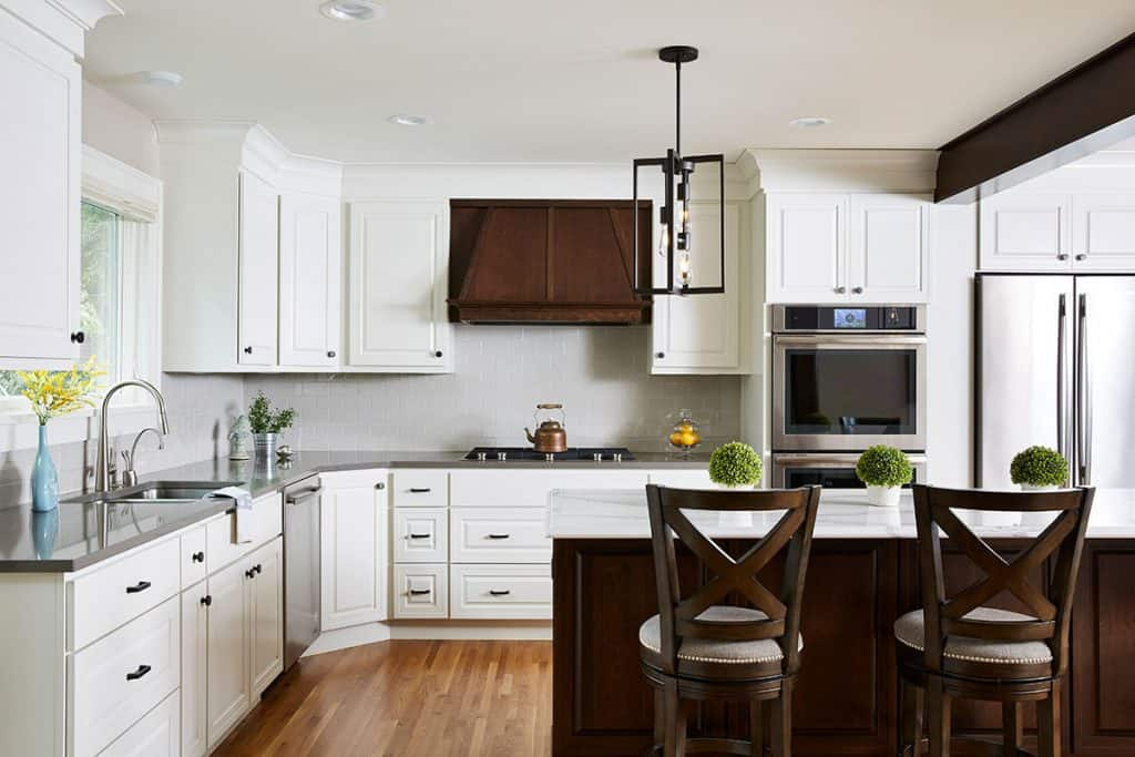 Kitchen remodel featuring white painted cabinets and cherry cabinet accents. Cambria countertops, Marvin windows, and stainless appliances.