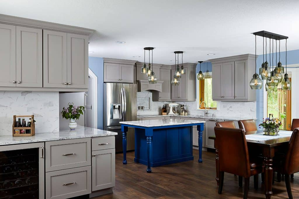 Kitchen remodel featuring painted cabinets, custom blue island, Cambria countertops, wood floors, guest entertaining bar.