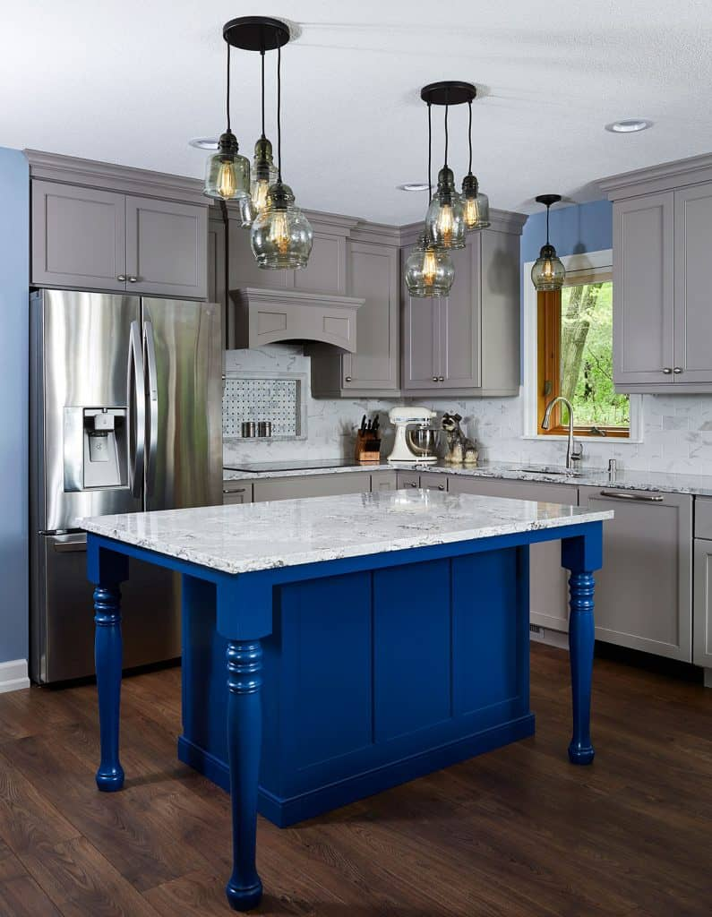 Custom blue painted island with Cambria countertops. Grey painted perimeter cabinets & marble tile backsplash. Wood flooring.