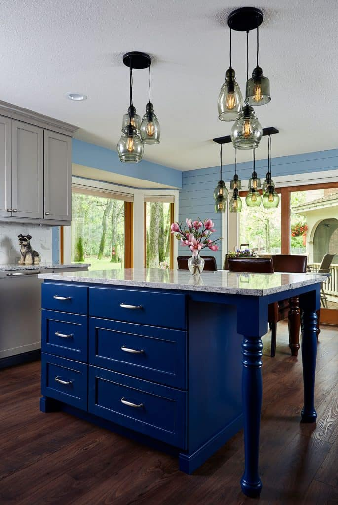 Custom blue painted island with Cambria countertops. Shiplap on dining room walls. Wood flooring.