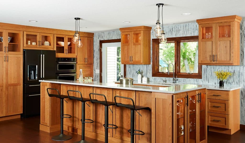 Kitchen featuring cherry cabinets, Cambria countertops, huge island, custom painted wall treatment, Marvin windows, and black stainless appliances.