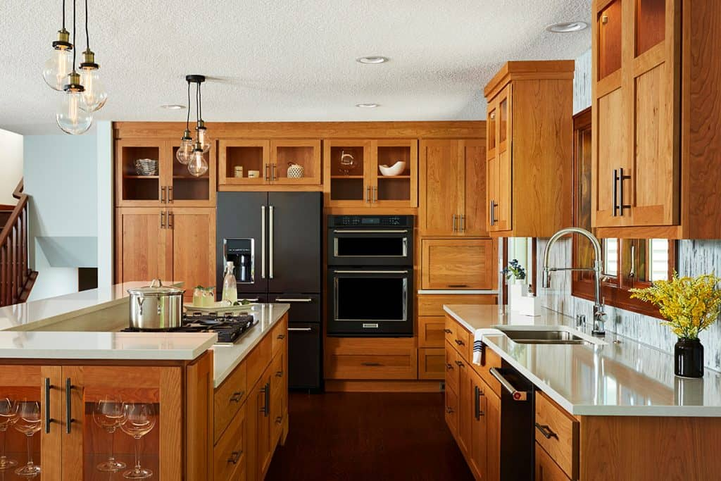 Kitchen featuring cherry cabinets, Cambria countertops, huge island, custom painted wall treatment and black stainless appliances.
