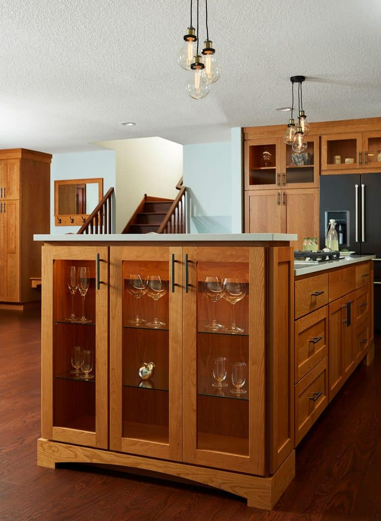 Large cherry island with lighted display cabinets, Cambria countertops, downdraft hood and tons of storage.