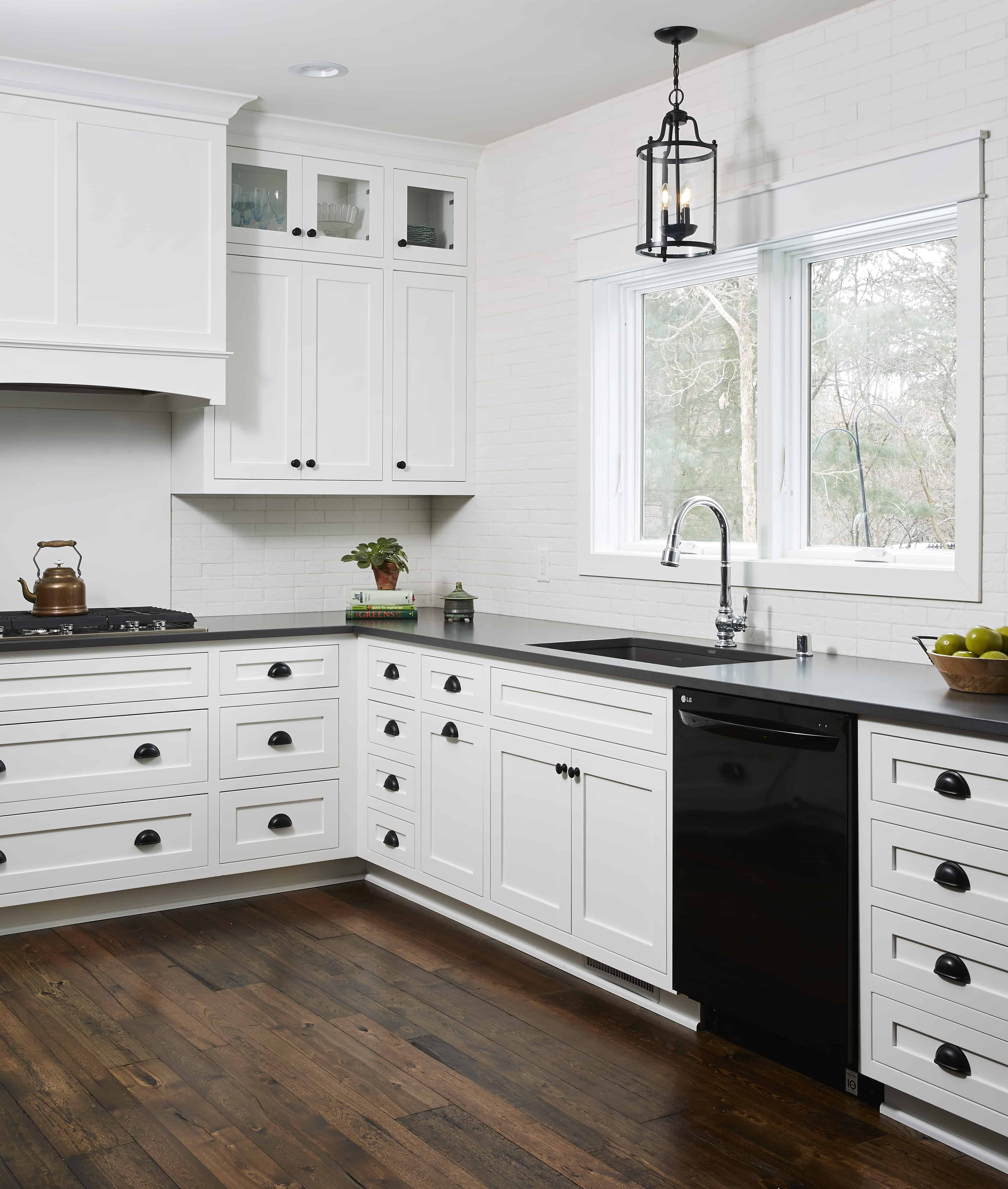White painted kitchen cabinets in a modern Cape Cod style. Wood hood and glass door accents. Black hardware & light fixture to coordinate with appliances. Antique elm flooring.