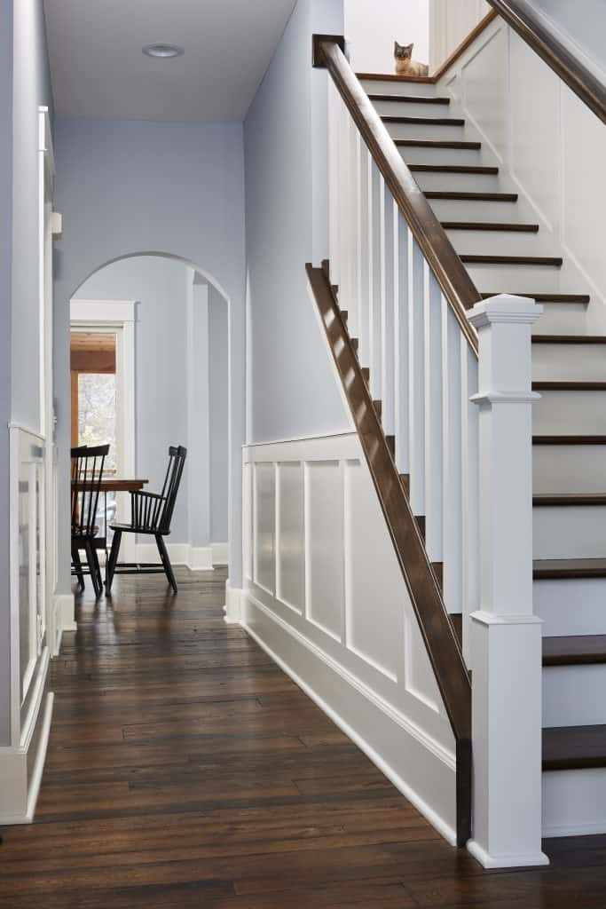White painted wainscot and new wood staircase add architectural interest to the front entry. Antique elm flooring adds warmth and character.