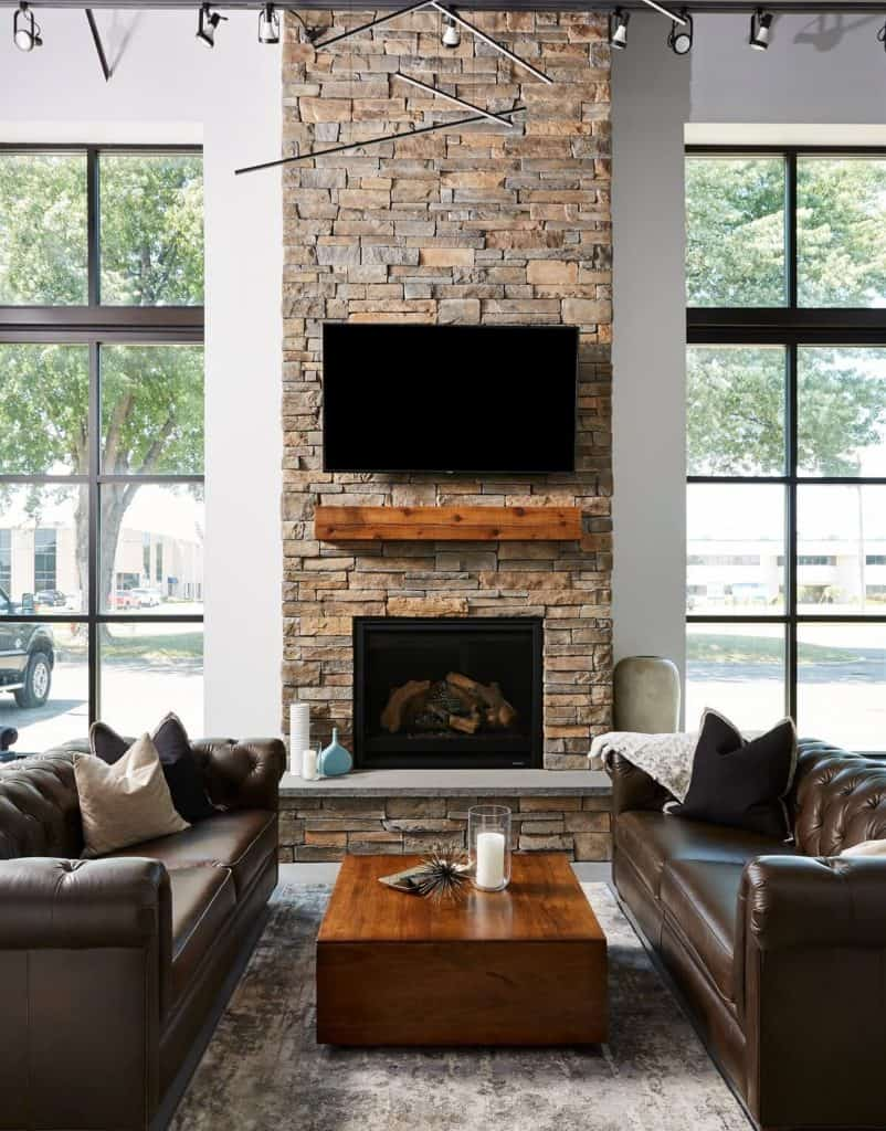 Stone fireplace flanked by expansive windows